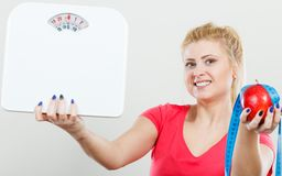 Woman holding apple,measuring tape and weight machine. Healthy fit lifestyle, getting ready for diet concept. Happy sporty woman holding red apple, measuring Royalty Free Stock Photography