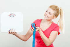 Woman holding apple,measuring tape and weight machine Royalty Free Stock Images