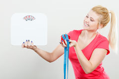 Woman holding apple,measuring tape and weight machine Stock Photography