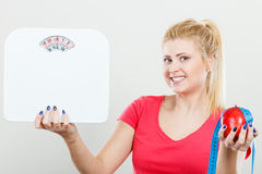 Woman holding apple,measuring tape and weight machine Stock Image