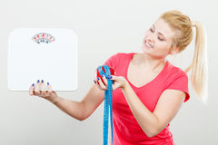Woman holding apple,measuring tape and weight machine Stock Images
