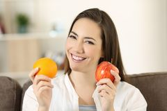 Woman holding an apple and orange looking at camera. Front view portrait of a happy woman holding an apple and orange looking at camera sitting on a couch in the Stock Photo