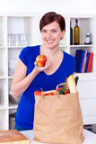 Woman holding an apple and shopping bag Royalty Free Stock Images