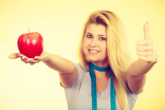 Woman holding apple showing thumb up Stock Photo