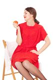 Woman holding an apple sitting on a chair Royalty Free Stock Photos