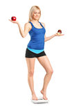 Woman holding an apple and slice of cake. A woman holding an apple and slice of cake, standing on a weight scale, isolated against white background Royalty Free Stock Image