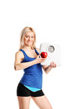 Woman holding an apple and a weight scale Royalty Free Stock Photography