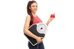 Woman holding an apple and a weight scale Royalty Free Stock Images