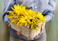 Woman holding arrangement of sunflowers in wooden box Royalty Free Stock Photography