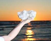 Woman holding Aurora Rainbow Quartz cluster from India in her hand at sunrise royalty free stock images