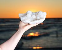 Woman holding Aurora Rainbow Quartz cluster from India in her hand at sunrise stock images