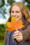 Woman holding autumn leaf Stock Photos