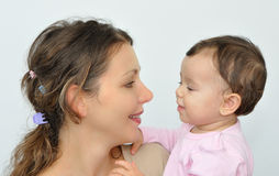 Woman holding a baby girl. Beautiful women holding a cute baby girl. They are looking at each other Stock Image