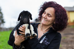 Woman holding a baby goat. Closeup portrait of a young woman holding a baby goat outdoor Royalty Free Stock Photo