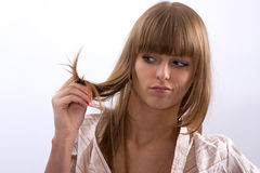 Woman holding bad hair in his hands. Woman in a stripy shirt holding bad hair in his hands Stock Photography