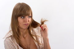 Woman holding bad hair in his hands. Woman in a stripy shirt holding bad hair in his hands Royalty Free Stock Images