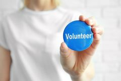 Woman holding badge with word VOLUNTEER. On light background stock photo