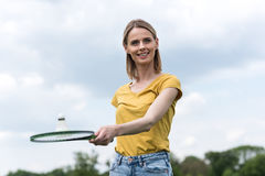 Woman holding badminton racquet with shuttlecock and looking away Stock Images