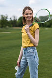 Woman holding badminton racquet and shuttlecock while looking away Royalty Free Stock Photo