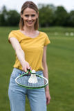 Woman holding badminton racquet with shuttlecock on the top Royalty Free Stock Photo