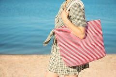 Woman holding bag on beach. Summer vacation stock photos