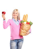 Woman holding a bag with groceries and an apple Royalty Free Stock Photo