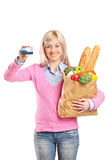 Woman holding bag with groceries and a blank card Royalty Free Stock Image