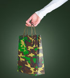 Woman holding a bag of military. Woman hand with Shopping bag on green background. gift for February 23 Royalty Free Stock Photos