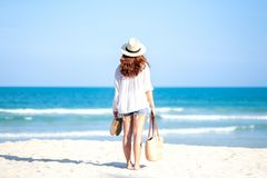 A woman holding bag and shoes while strolling on the beach. With the sea and blue sky background stock photos