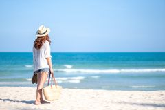 A woman holding bag and shoes while strolling on the beach. With the sea and blue sky background stock image