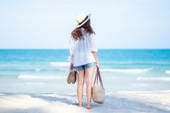 A woman holding bag and shoes while strolling on the beach. With the sea and blue sky background royalty free stock photos
