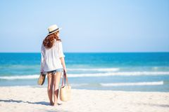 A woman holding bag and shoes while strolling on the beach. With the sea and blue sky background royalty free stock photography
