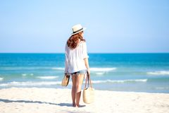 A woman holding bag and shoes while strolling on the beach. With the sea and blue sky background royalty free stock images