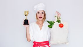 Woman holding bag with vegetables and prize cup Stock Photos