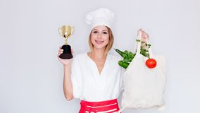 Woman holding bag with vegetables and prize cup Stock Photo