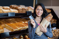 Woman holding baguettes and credit card at bread counter Royalty Free Stock Image