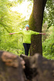 Woman holding balance on tree trunk in nature. Stock Photography