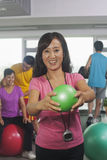 Woman holding ball on foreground, people working out in the gym on the background Royalty Free Stock Photo