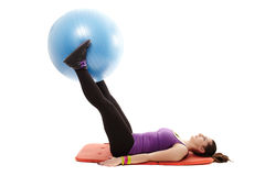 Woman holding a ball between legs and working her abdominal musc Stock Photo