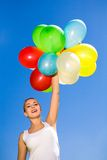 Woman holding balloons against blue sky. Young woman holding balloons against blue sky Stock Photo