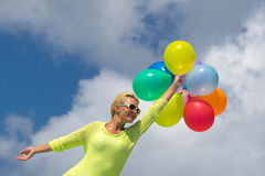 Woman holding balloons against cloud Royalty Free Stock Photo