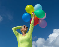 Woman holding balloons against cloud Stock Photos