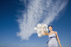 Woman Holding Balloons Against Sky. Portrait of happy young woman holding balloons against sky Royalty Free Stock Images