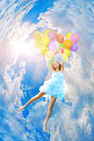 Woman holding balloons against sun Stock Images