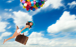 Woman holding balloons and flying above clouds. Young woman holding balloons and old suitcase, flying above clouds. Concept of travel and freedom Royalty Free Stock Photography
