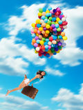Woman holding balloons and flying above clouds. Young woman holding balloons and old suitcase, flying above clouds. Concept of travel and freedom Royalty Free Stock Images