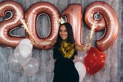 Woman holding balloons looking at camera. Celebration holiday new year royalty free stock photo