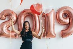 Woman holding balloons looking at camera. Celebration holiday new year royalty free stock photography