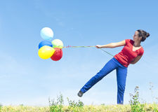 Woman holding balloons on wind Stock Photo