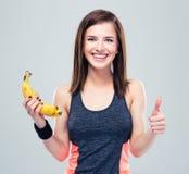 Woman holding banana and showing thumb up. Happy cute woman holding banana and showing thumb up over gray background. Looking at camera Royalty Free Stock Photography